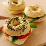 homemade mini bagels stuffed with tomato, mozzarella and basil leaves.