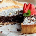 nutella tart topped with strawberries, confectioner's sugar and chopped almonds