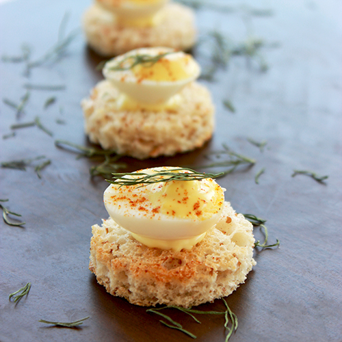 three deviled quail eggs placed over toasted bread cut into rounds.