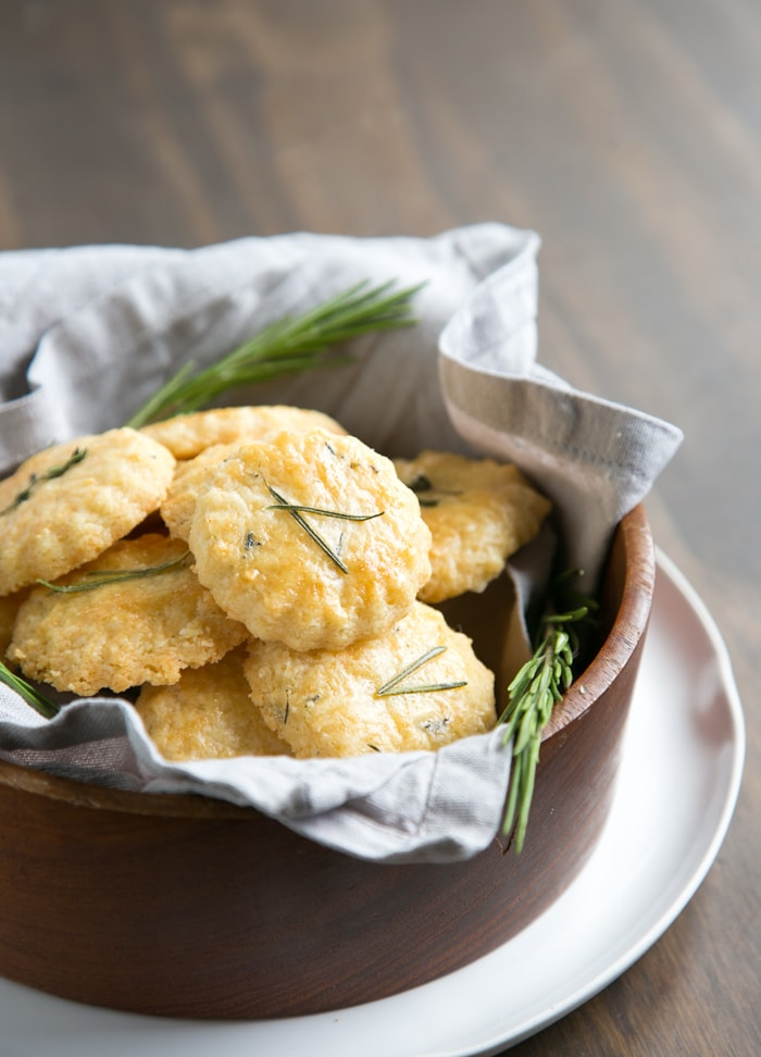 Parmesan cookies in a large wooden bowl covered with grey napkin, white plate beneath and wood table in the background.