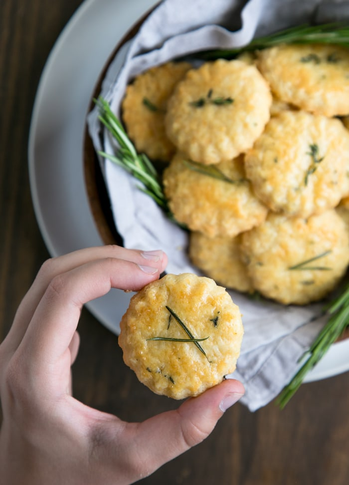 hand holding a parmesan cookies, plate with parmesan cookies and rosemary sprigs in the background.