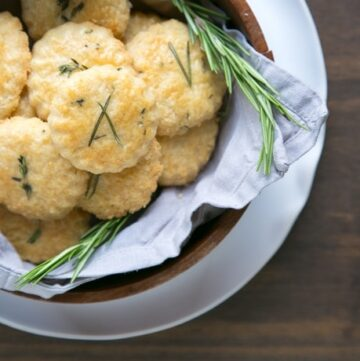 parmesan cookies and rosemary sprigs in a wood bowl covered with grey napkin, white plate beneath on wood table.