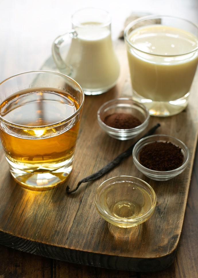 ingredients for homemade baileys: whiskey, condensed milk. cocoa powder, instant coffee, agave syrup, vanilla pod, heavy cream.