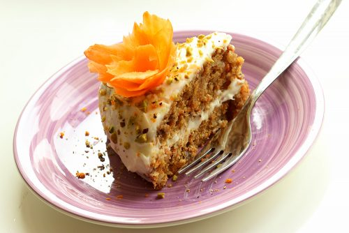 slice of easy carrot cake with orange mascarpone cream in a purple dish with fork