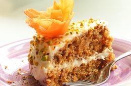 slice of easy carrot cake with orange mascarpone cream on a purple plate with fork next to it