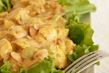 Coronation Chicken on a bed of salad leaves with fork on the right side