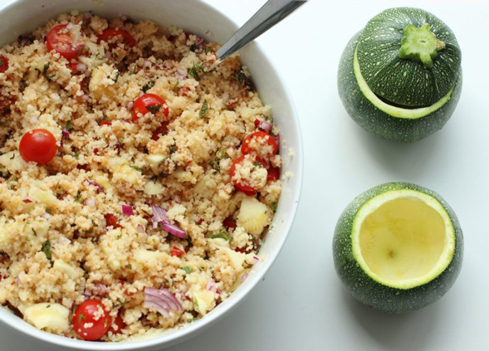 couscous salad in a bowl and round zucchini ready to be stuffed next to the bowl.