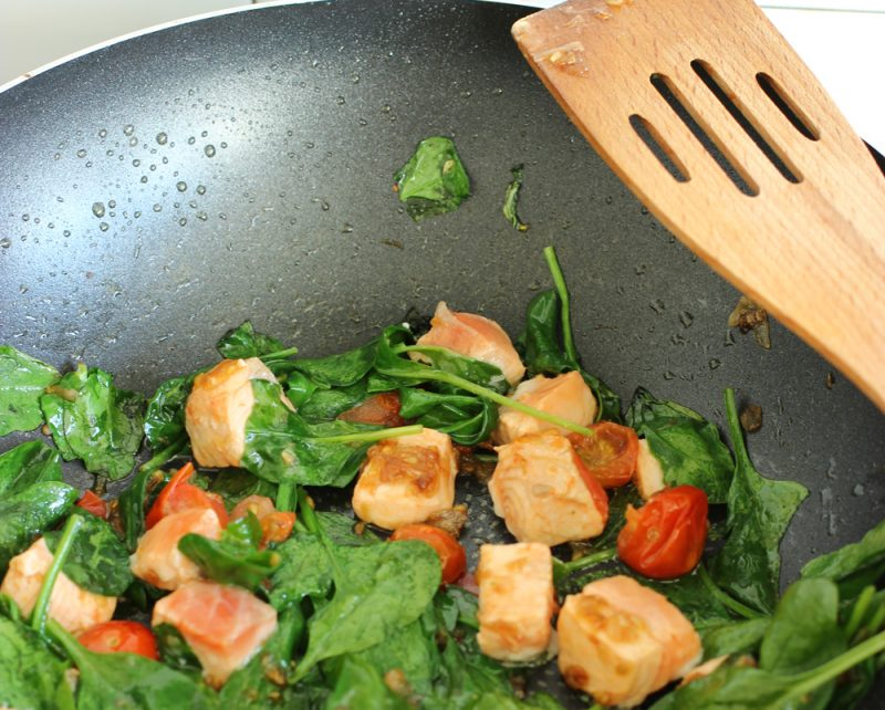 salmon cubes, spinach leaves and cherry tomatoes cooking in a pan