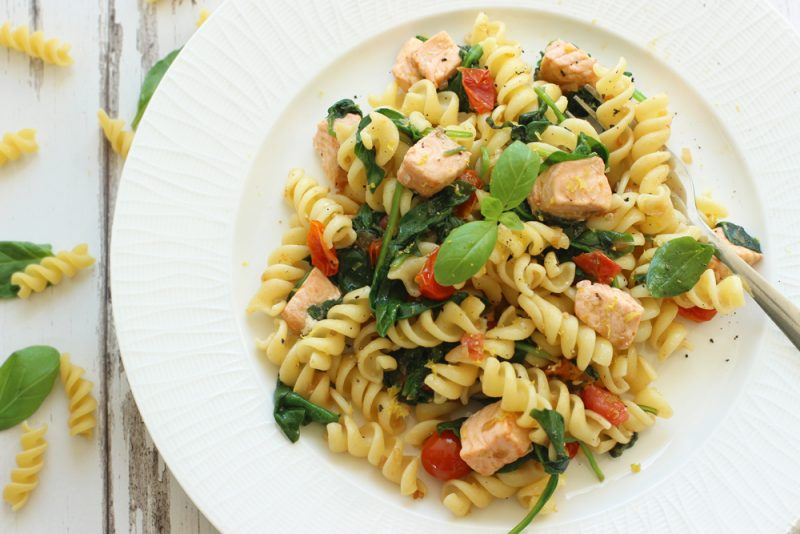 salmon spinach pasta on a white plate