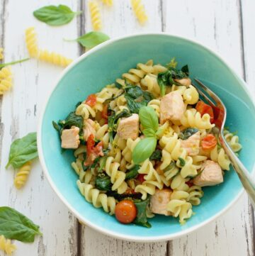 salmon spinach pasta in a light blue bowl
