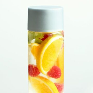 orange and raspberry fruit water in a glass bottle