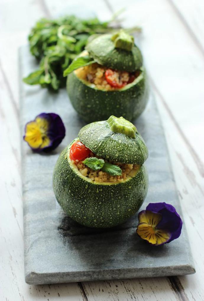 two couscous salad stuffed round zucchini.
