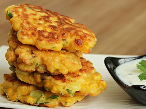Sweetcorn Fritters on a white plate next to yogurt dip in a small black bowl