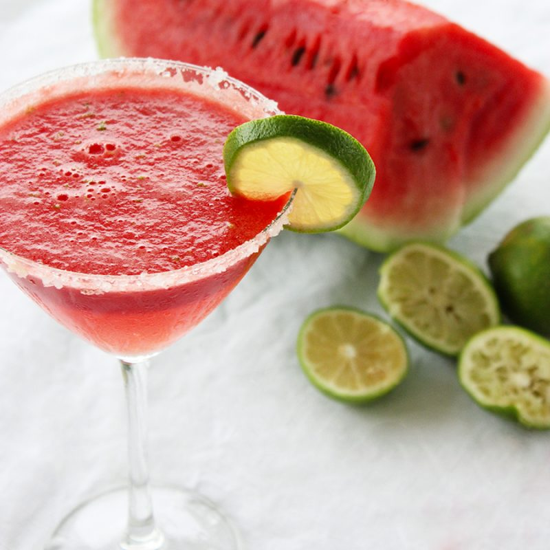 watermelon margarita served in a martini glass and decorated with a lime slice.