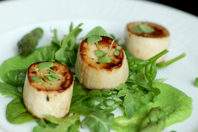 vegan scallops with pea pesto, baby salad leaves and asparagus.