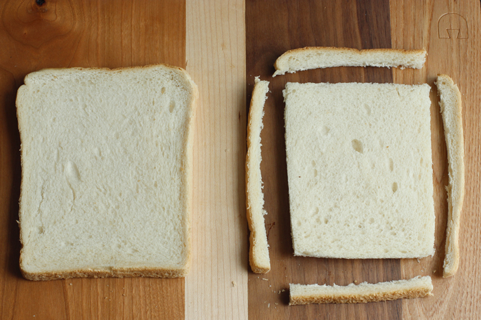 recipe step one: two white bread slices on wood board, one with the crust cut off