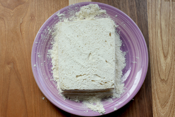italian fried mozzarella sandwich prep step 3 : filled sandwich dusted with flour on a purple plate