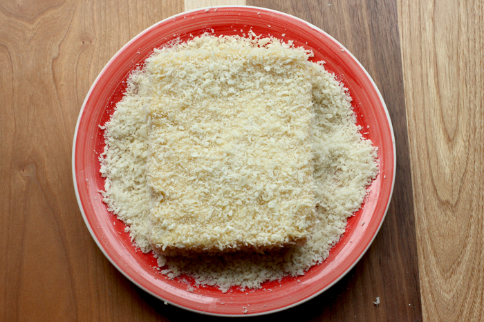 deep fried mozzarella sandwich prep step 5: sandwich coated in breadcrumbs on a red plate