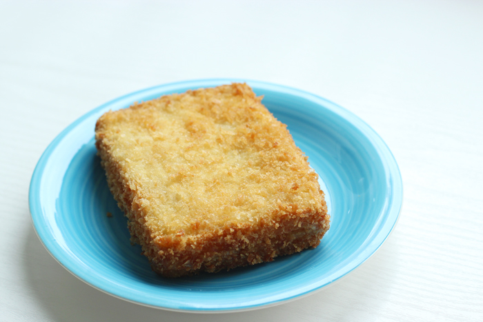 fried mozzarella sandwich on a light blue plate, white background