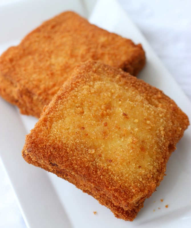 two fried mozzarella sandwiches on a white plate