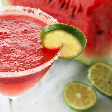 Watermelon margarita served in amartini glass and decorated with a lime slice.