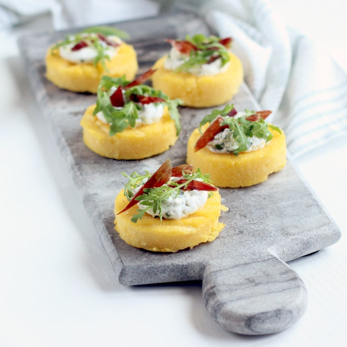 These polenta crostini scream summer at every bite. Light and refreshing, this simple yet elegant starter is also naturally gluten free and features ricotta, jamon and fresh rocket. Recipe from thepetitecook.com