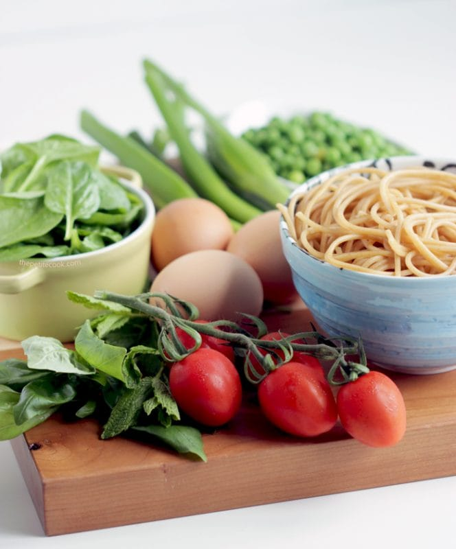 tomatoes on the vine, basil leaves, spinach leaves, eggs, peas, cooked spaghetti on a wood board