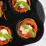 spaghetti cupcakes topped with ricotta and basil in a muffin tin