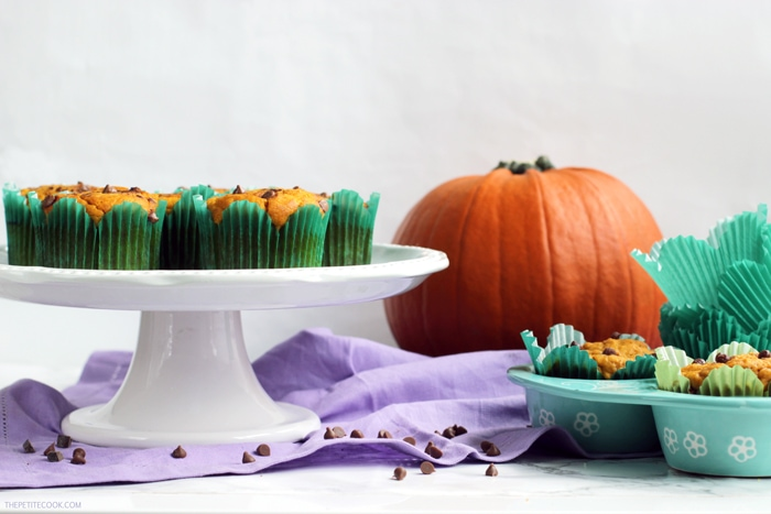 dairy-free pumpkin muffins on a cake stand and on a muffin tin, pumpkin in the background