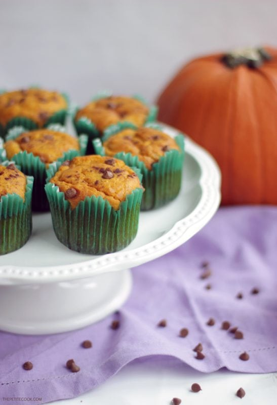 dairy-free pumpkin muffins on a cake stand, pumpkin in the background