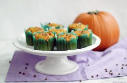 dairy-free pumpkin muffins on a cake stand next to a pumpkin