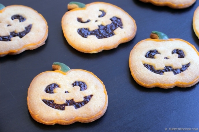 Pumpkin-shaped Halloween Italian Shortbread Cookies recipe on black background next to half pumpkin