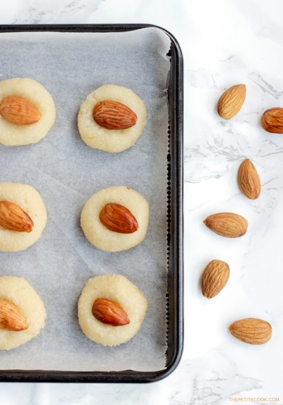 recipe step 5: almond cookies arranged on a baking tray covered with parchment paper, ready to go in the oven