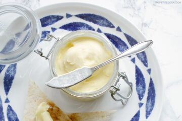 homemade butter in jar with knife over it, bread toasted with butter on top on a large white and blue plate, image optimized for Pinterest