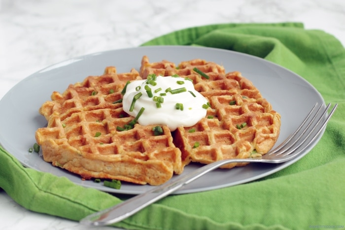large sweet potato waffle topped with sour cream and chive, served on a plate