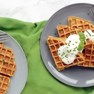 sweet potato waffles topped with sour cream and chives served onto two plates.