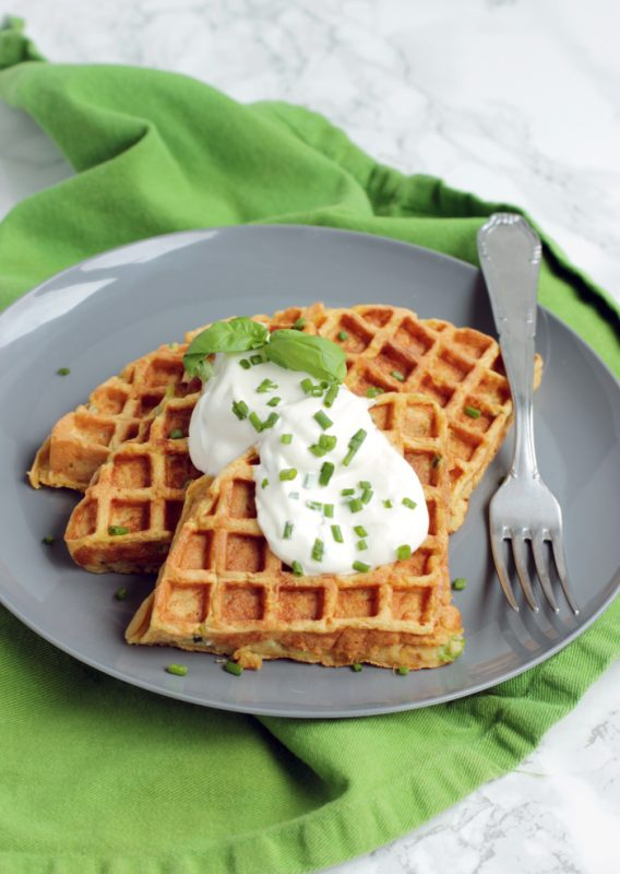 Three sweet potato waffles topped with sour cream and chives, served on a plate.