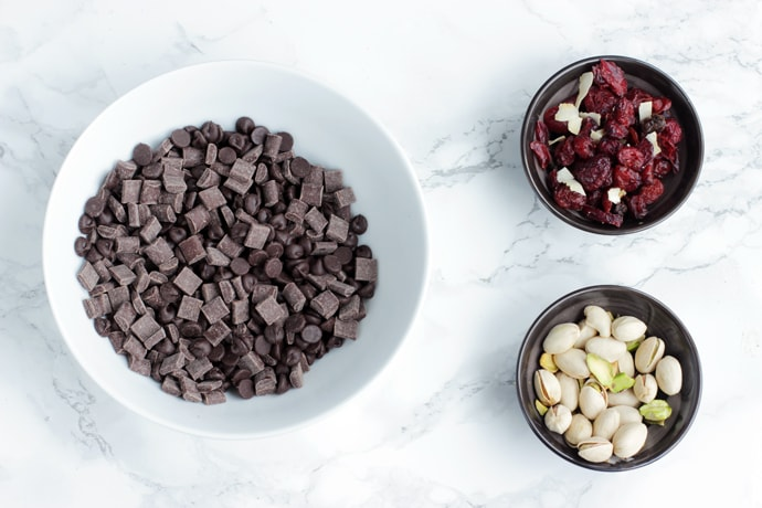 chocolate chips in one bowl, next to dried cranberries in a small bowl, next to pistachios into another small bowl.
