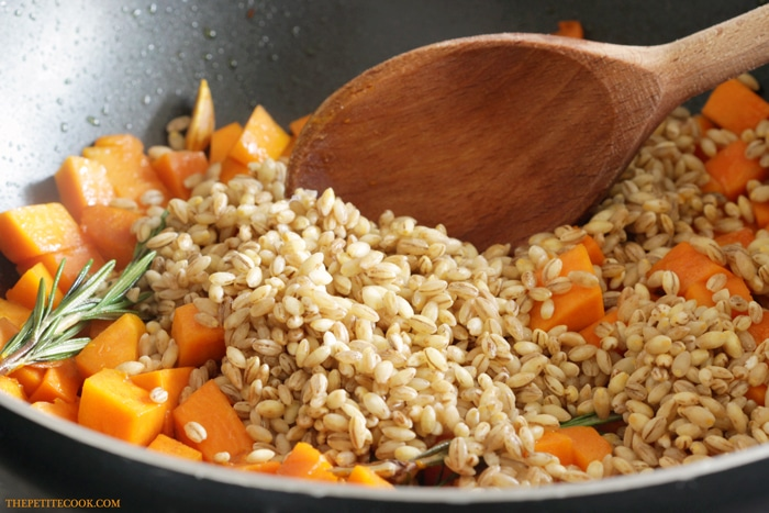 barley in a pan with pumpkin cubes and rosemary sprig, wood spoon stirring the mixture for barley risotto with pumpkin