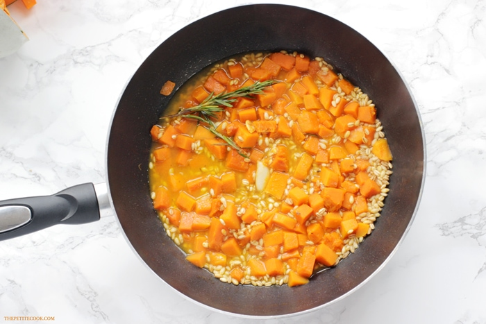 Barley Risotto with Pumpkin and Rosemary cooking in a pan