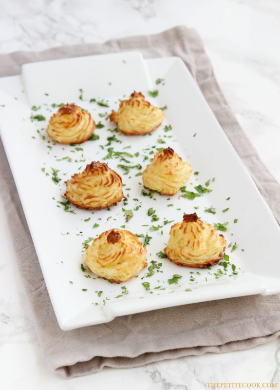 Easy duchess potatoes decorated with parsley on a large white serving dish over a beige napkin