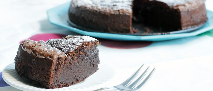 2-ingredient nutella cake slice in the focus with fork next to it, cake in the background on a turquoise plate.
