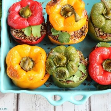 6 quinoa stuffed bell peppers in a large baking dish, next to lime wedges and bunch of cilantro