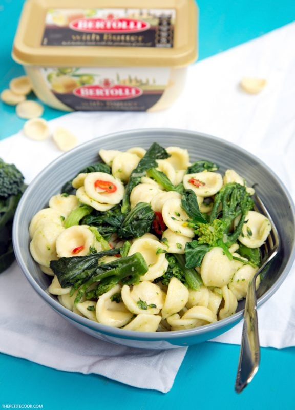 orecchiette with broccoli and choy sum in a bowl with a fork, bertolli packaging in the background