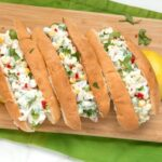 three summer lobster rolls on a wood board