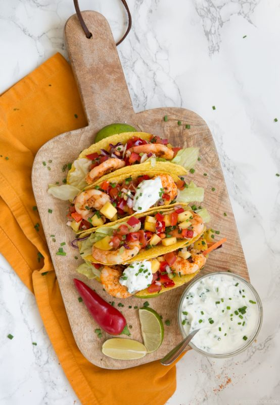 Give a vibrant refreshing twist on a Mexican favorite and try these Spicy Shrimp Tacos with Mango Salsa - The perfect Summer bite to share with friends! Recipe from thepetitecook.com