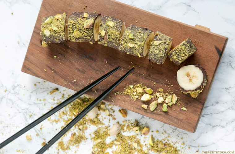 Pistachio Chocolate Banana Sushi on a wood board with chopsticks on the side