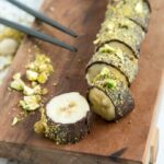 banana sushi on a wood board, black chopsticks next to it and crumbled pistachio over the marble background