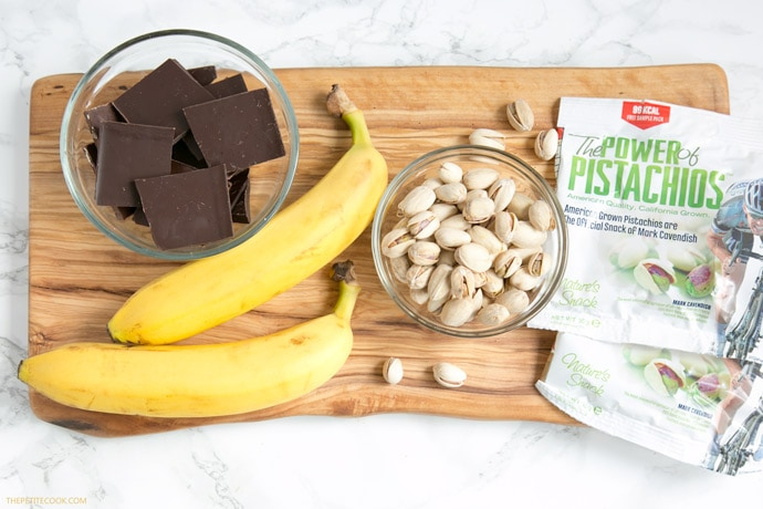recipe ingredients: chopped dark chocolate, banana, pistachios on a wood board