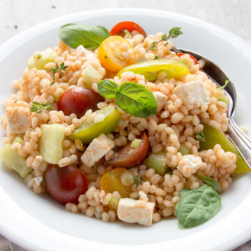 greek barley salad in a plate topped with basil leaves
